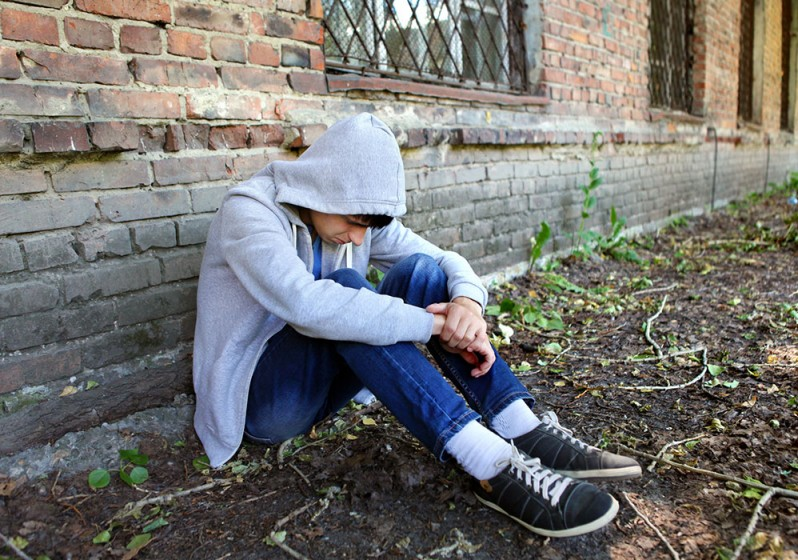 Depressed young man sitting next to wall