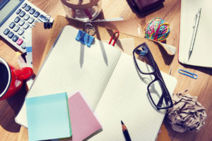 Cluttered desk with notepad, sticky notes, glasses etc.