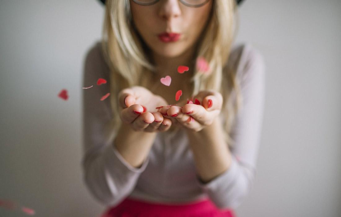 Girl blowing confetti hearts