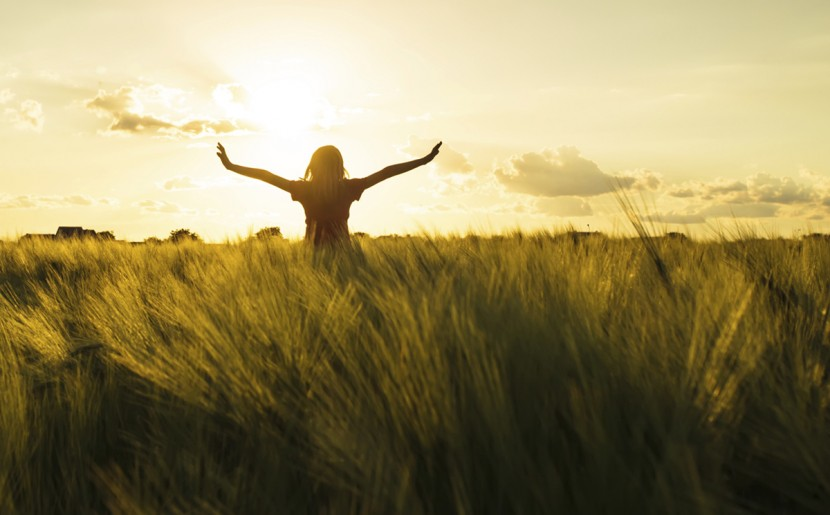 Happy, liberated girl in a grassy field at sunset.