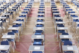 Rows of empty desks and chairs in an exam hall.