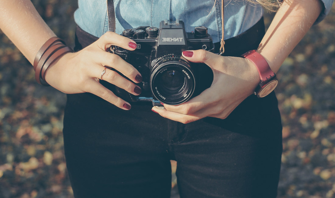 girl with red nails holding camera