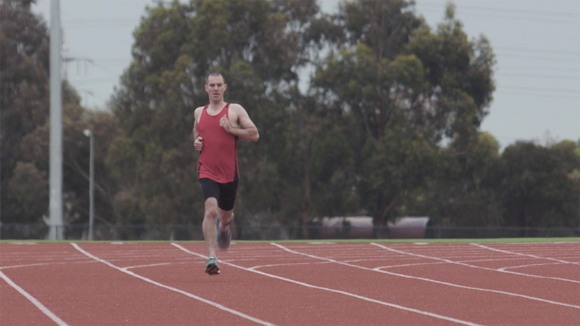 Image of a man running on a running track