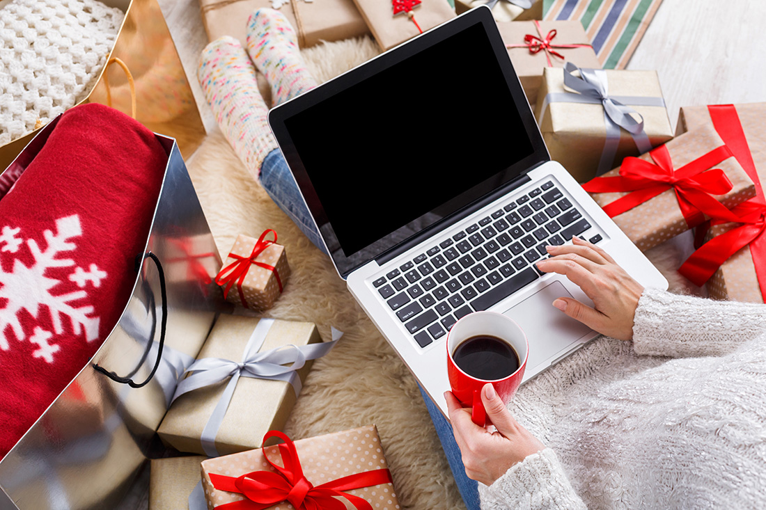 Woman on a laptop doing Christmas shopping online, sitting among wrapped presents.