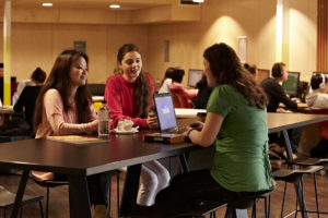 Three students chatting around a table on campus