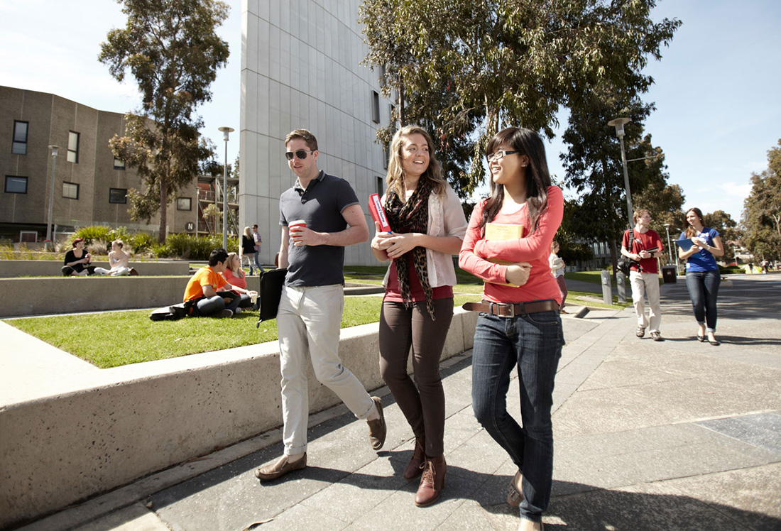 Three students walking on a university campus.