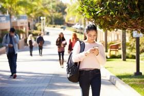 Student walking through university camus looking at phone.