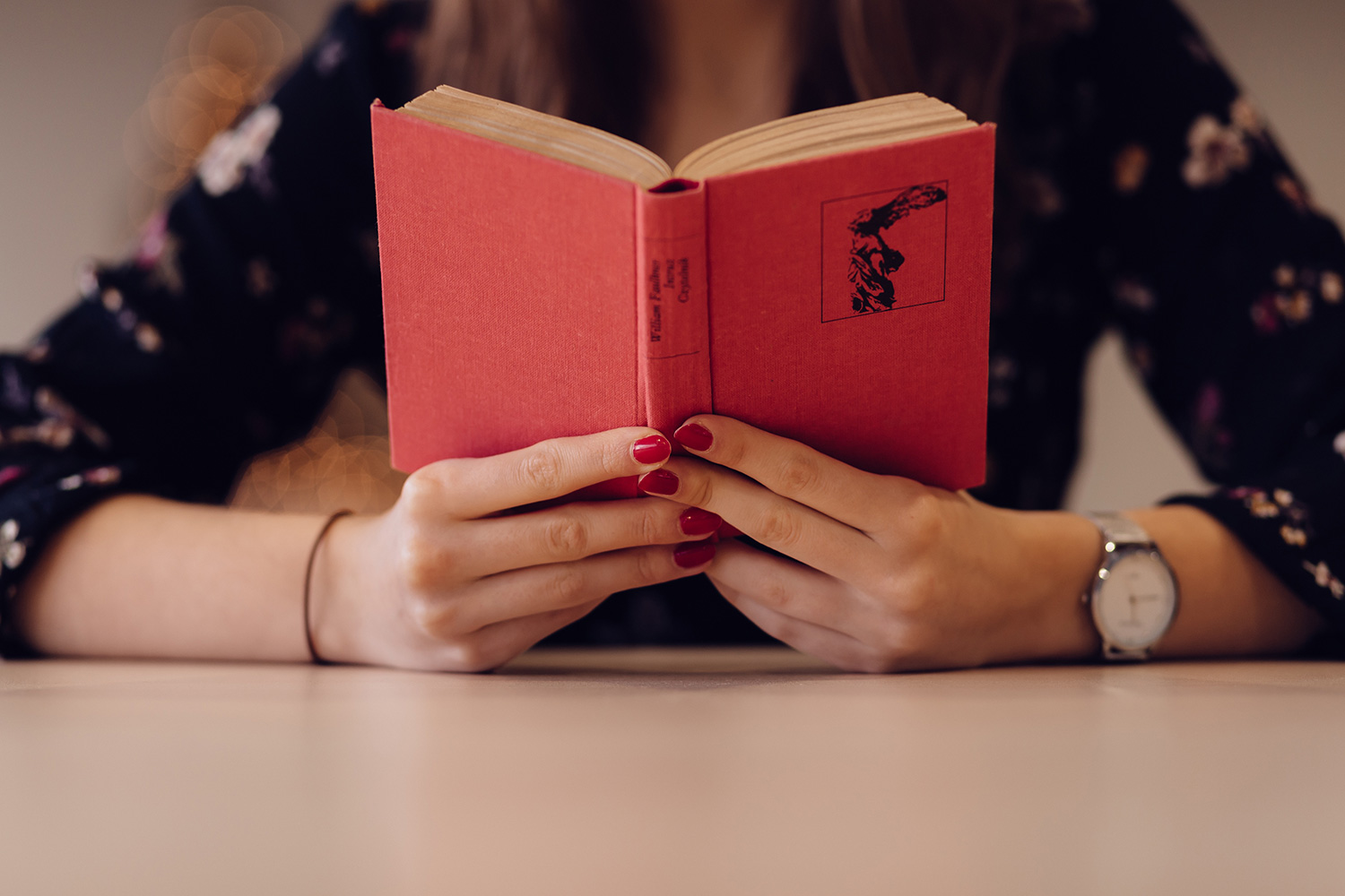 Close up of a student reading a red hard-covered book.