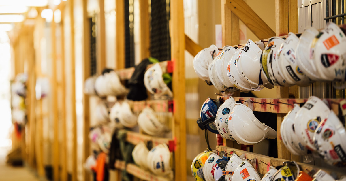 A construction site, with helmets hanging on hooks inside.