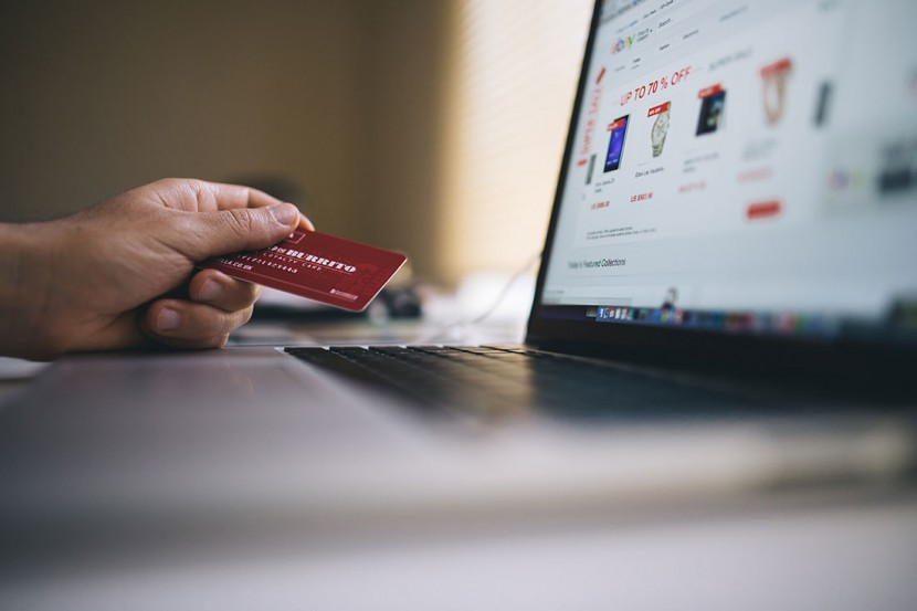 Person entering credit card details for online purchase.
