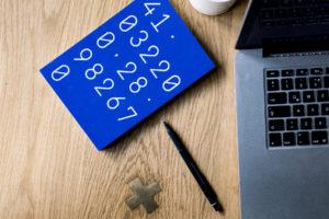 maths workbook, pen and laptop