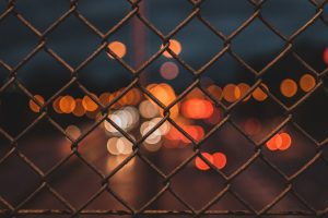 a chain fence with lights behind it.