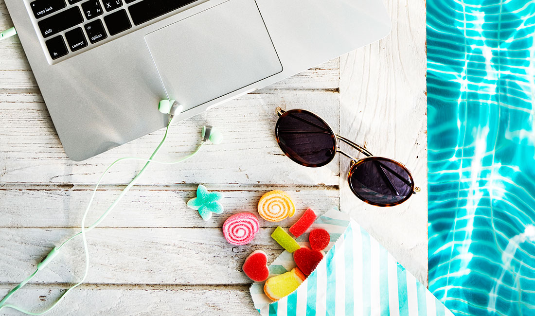 Laptop, sunglasses and lollies next to pool.