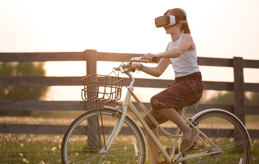 girl with VR goggles on bike