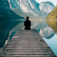 Person meditating at a lake