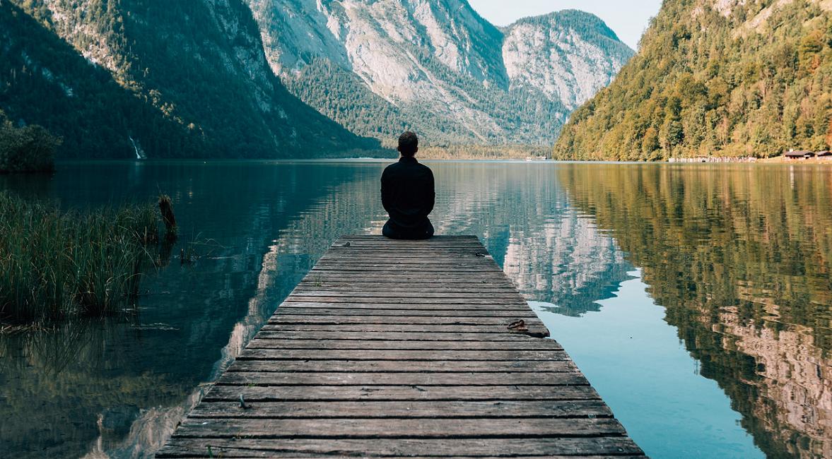 Person meditating at a lake