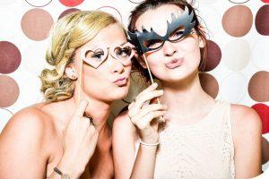 Two women wearing masquerade masks