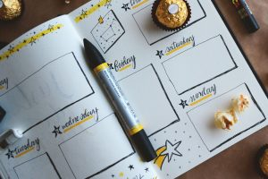weekly planner with pens and snacks scattered on planner