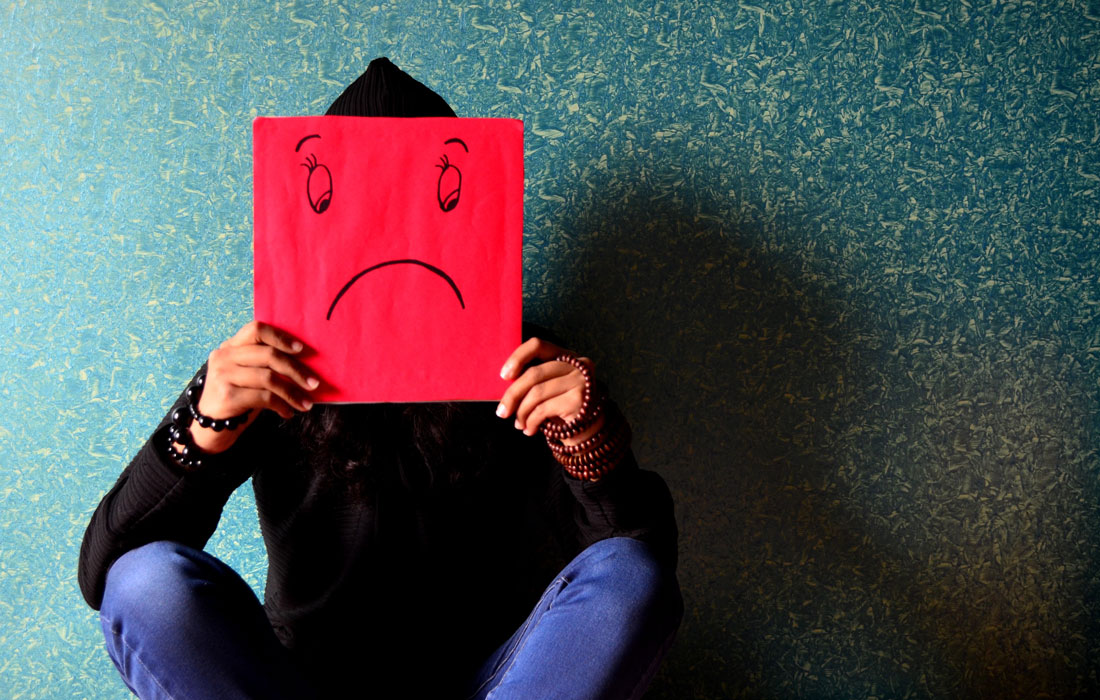 person holding paper with unhappy face drawing