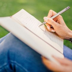 hand writing in notebook outdoors