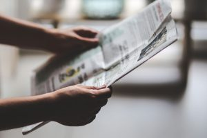 hands reading newspaper