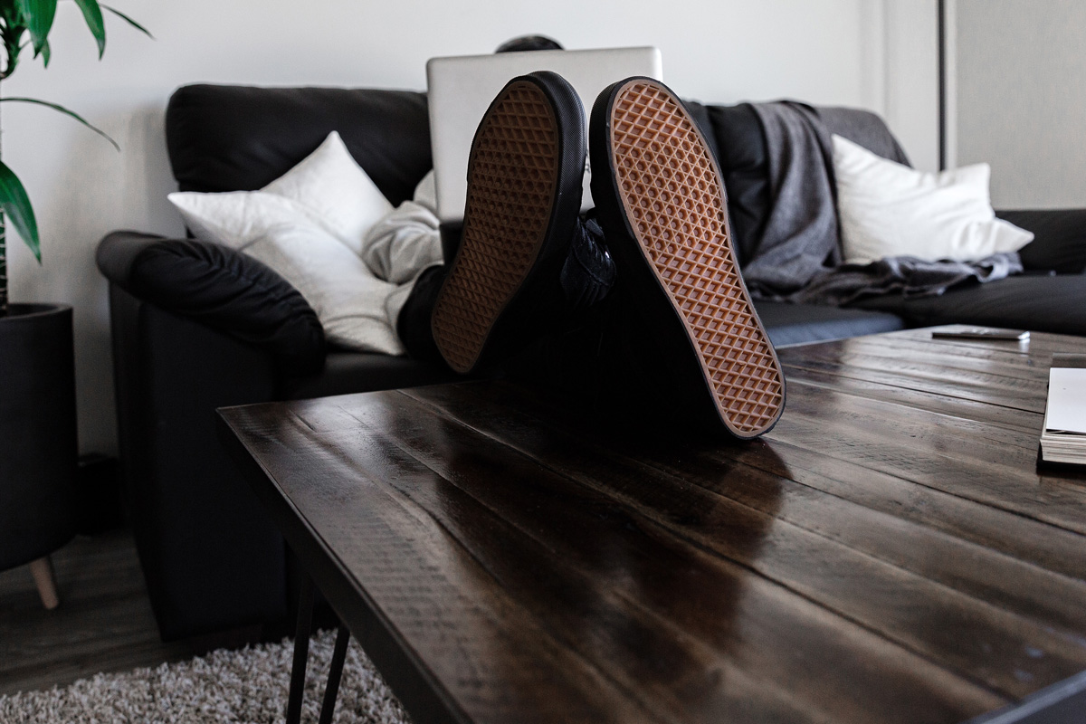 Man working from his couch with his feet up on a table