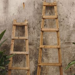 two ladders leaning against wall