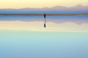 woman standing on salt lake reflection