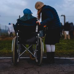 A woman standing beside someone in a wheelchair