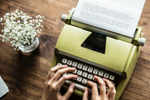 Person writing on a typewriter
