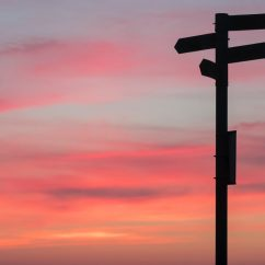 Signpost silhouetted against a sunset