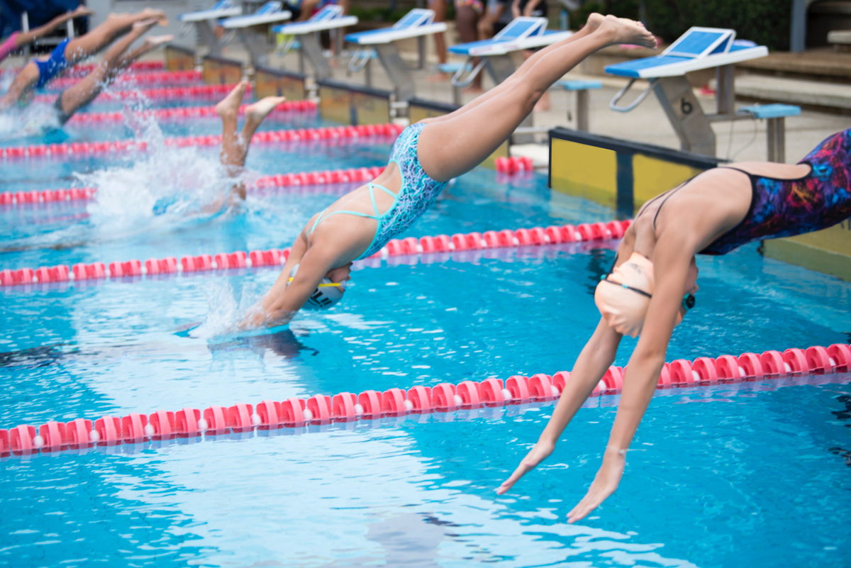 Women diving into a swimming pool