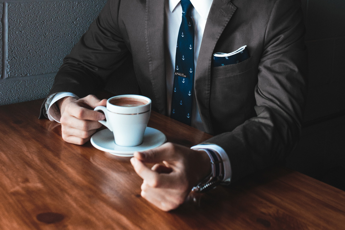 A man in a suit drinking coffee