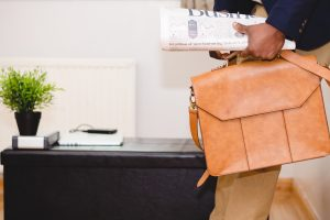 Man carrying briefcase and business newspaper