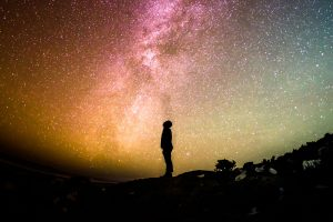 Silhouette of person against a bright night sky