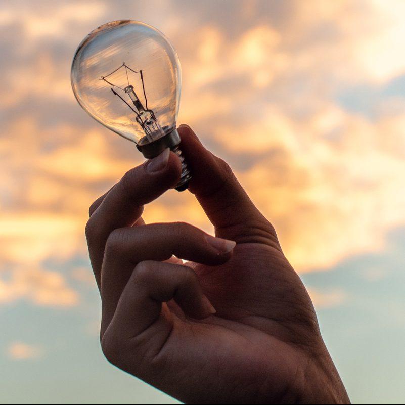 Hand holding light bulb against a sunrise