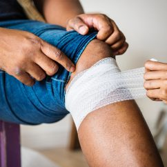 person bandaging a knee