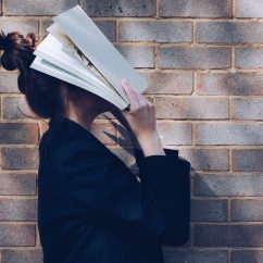 Woman holding a textbook on her face