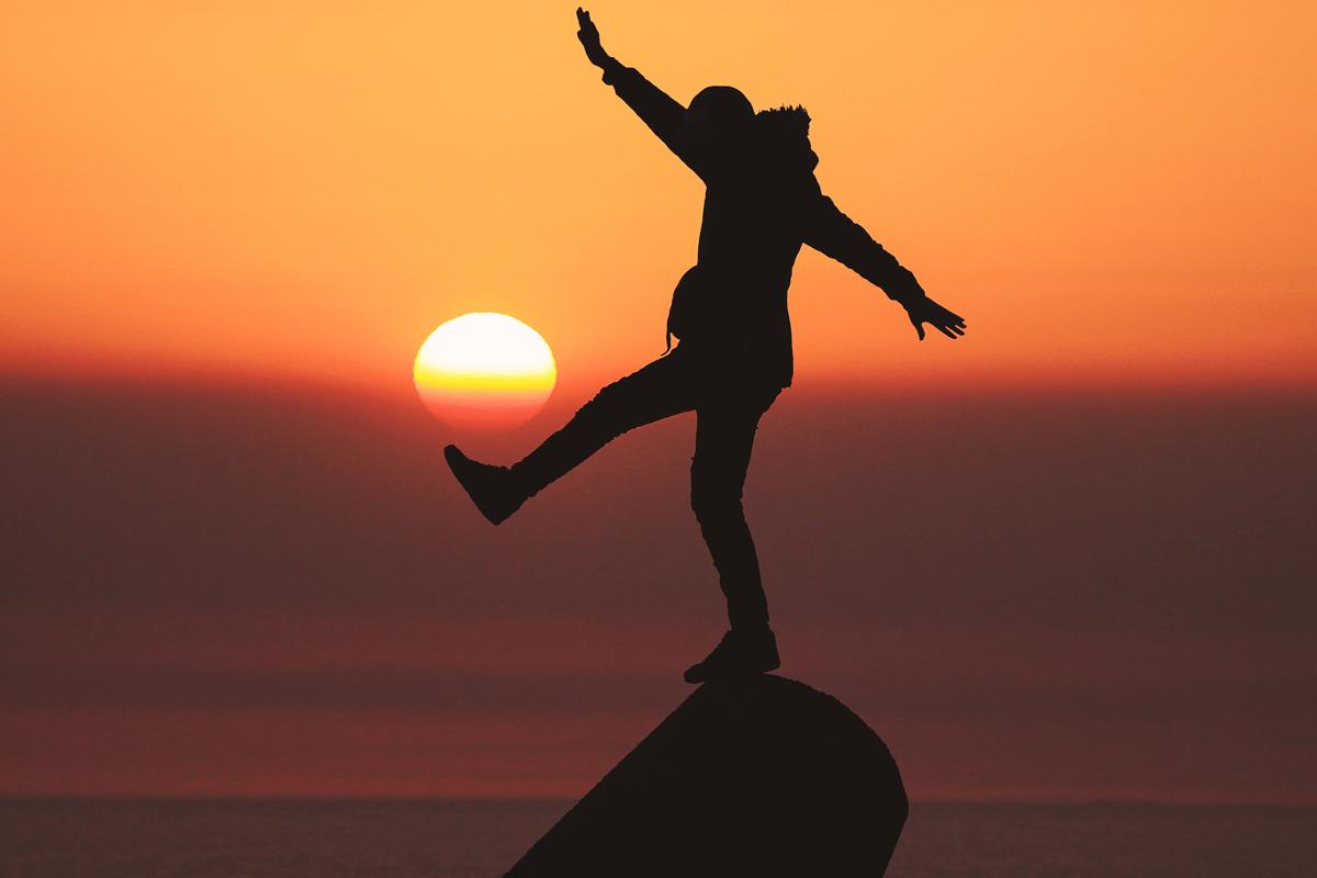 Person's silhouette kicking the sun