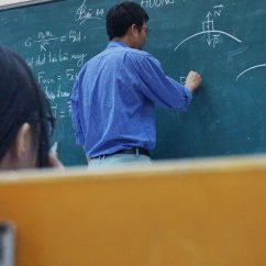 male teacher writing on a blackboard