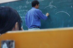 male teacher writing on a blackboard