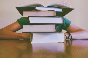 person slouching behind a stack of books