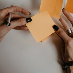 Person's hands holding blank sticky notes