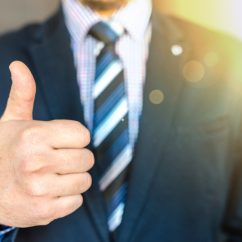 Thumbs up by a person in suit