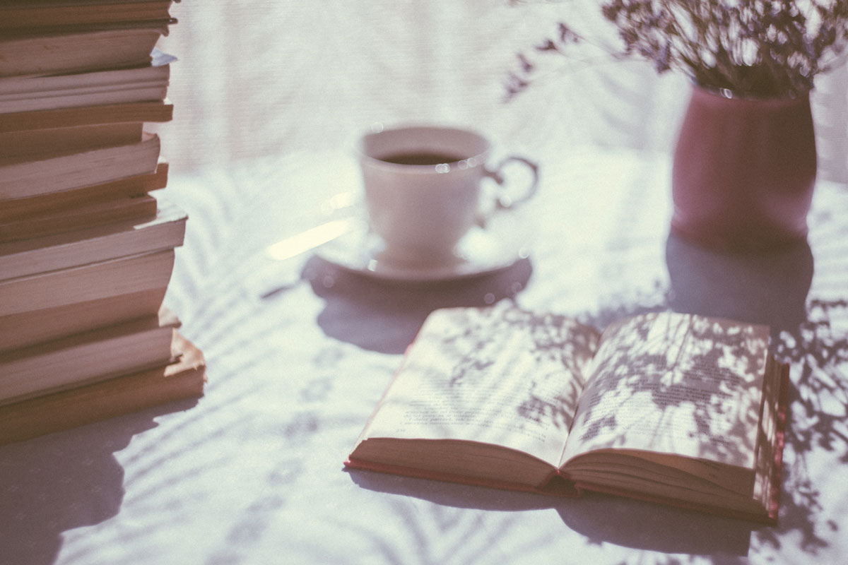 Open book beside a coffee cup