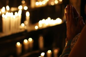Person in prayer facing candles