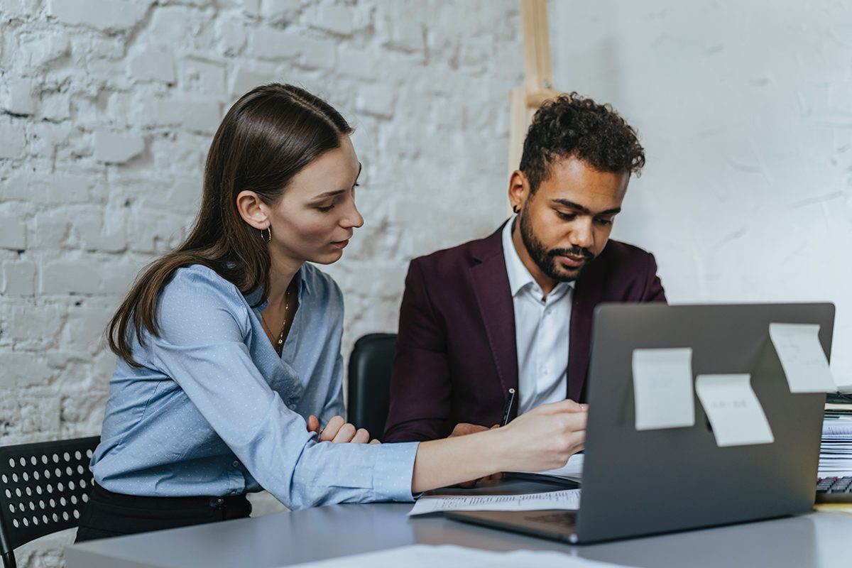 Woman and man working together in front of a laptop and notes