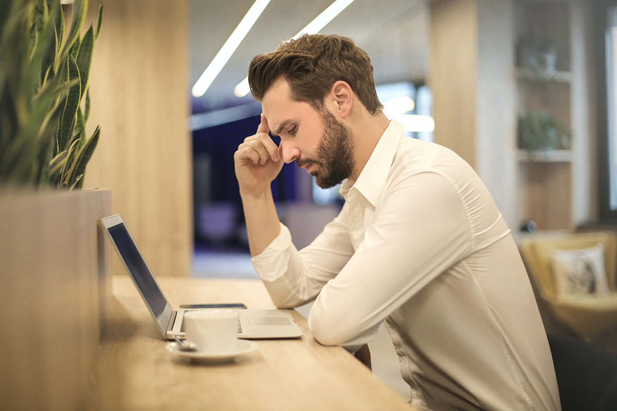 Man sitting in front of laptop with his hand on his head