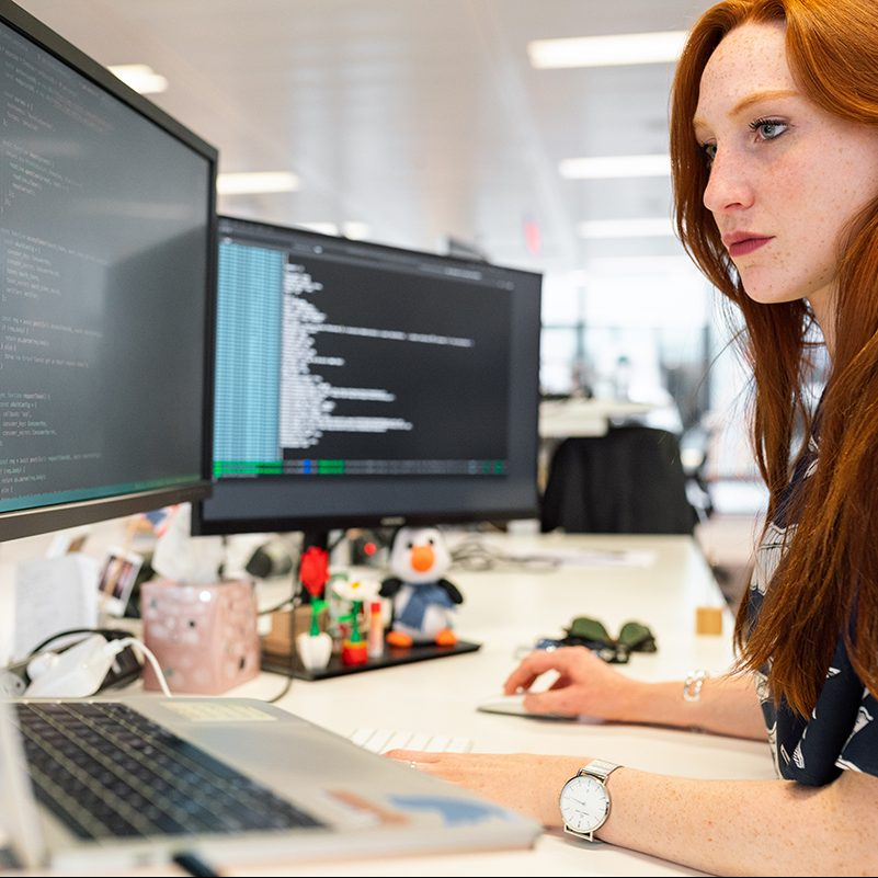 Woman sitting in front of two computer screens displaying code