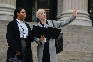 Woman holding a black folder and gesturing to something to woman standing next to her